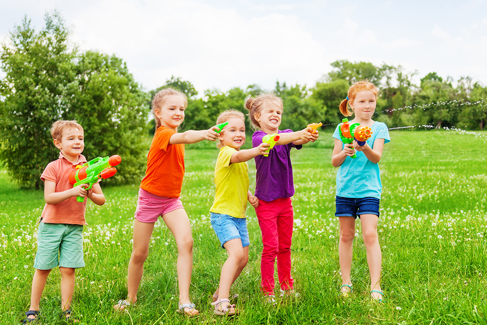 Kids playing outdoors with water guns on a beautiful sunny day